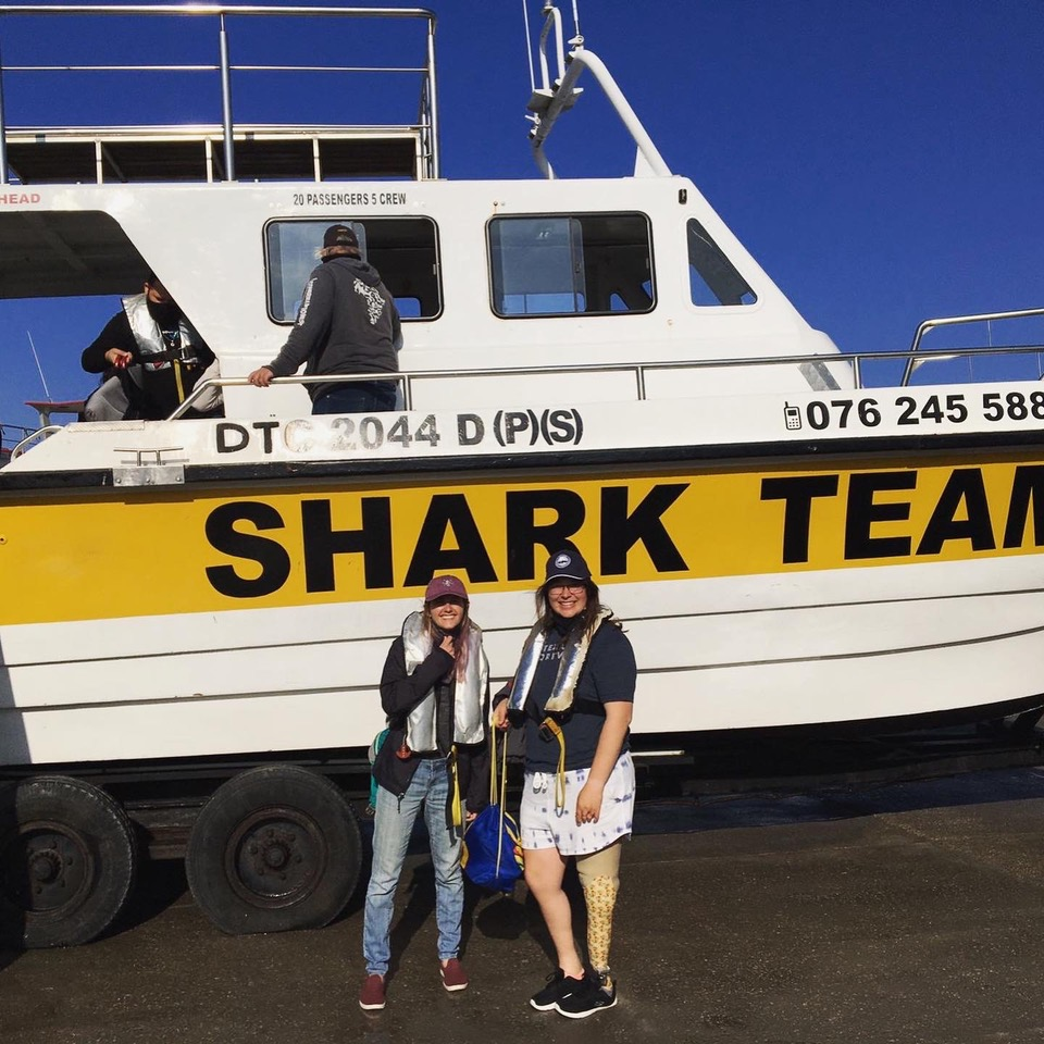 Students posing in front of a cage diving boat in Gansbaai.